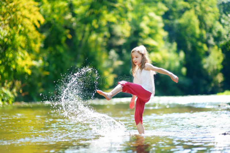 Nettes kleines Mädchen, das Spaß durch einen Fluss am warmen Sommertag hat lizenzfreie stockbilder