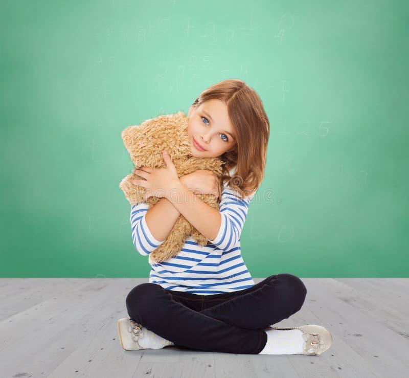 Nettes kleines Mädchen, das Teddybären umarmt stockbilder