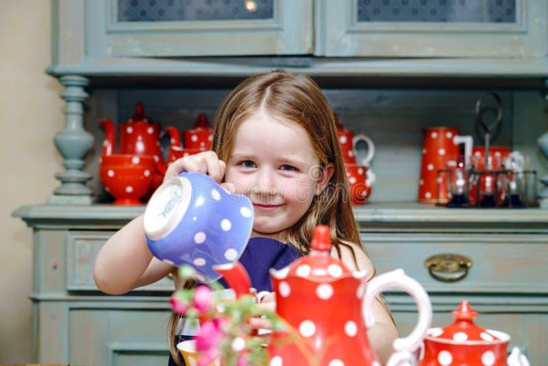 Nettes kleines Mädchen, das Tee in der Teekanne zubereitet stockfotos