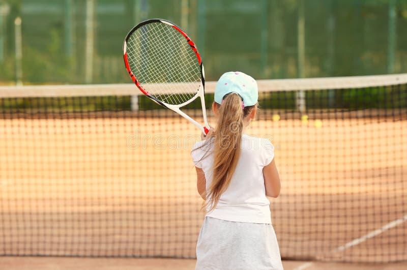 Nettes kleines Mädchen, das Tennis auf Gericht spielt stockbilder