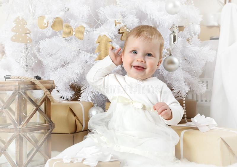 Nettes kleines Mädchen, das unter einem Weihnachtsbaum sitzt stockbilder
