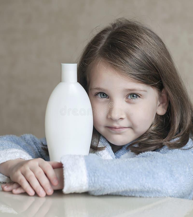 Nettes kleines Mädchen, das verschiedene weiße Schönheitstoilettenartikel in ihren Händen, die Kamera betrachtend hält Babybad, H stockbilder