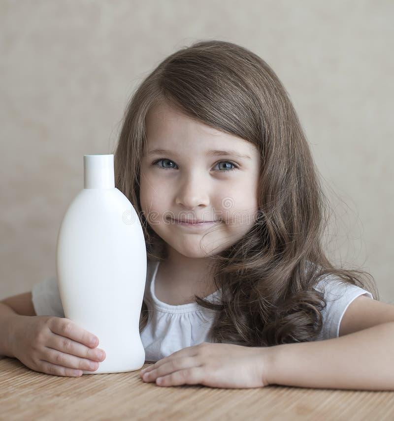 Nettes kleines Mädchen, das weiße Plastikshampooflasche in ihren Händen, die Kamera betrachtend hält Babybad, Hygienezubehör lizenzfreie stockfotografie