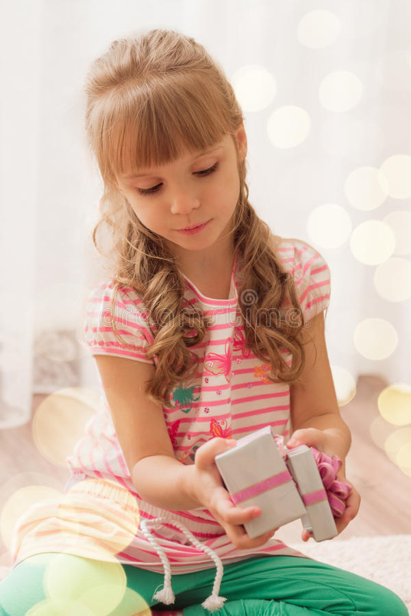 Nettes kleines Mädchen, das zu Hause eine kleine Geschenkbox öffnet Feiertagslicht stockfoto