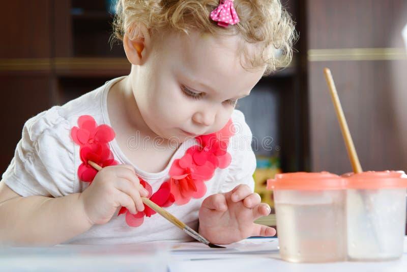 Nettes kleines Mädchen, das zu Hause malt lizenzfreies stockfoto