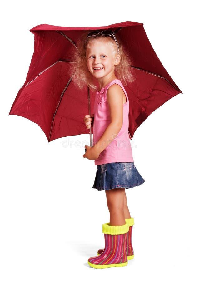 Nettes kleines Mädchen in den Gummistiefeln mit Regenschirmstellung lokalisiert lizenzfreies stockfoto