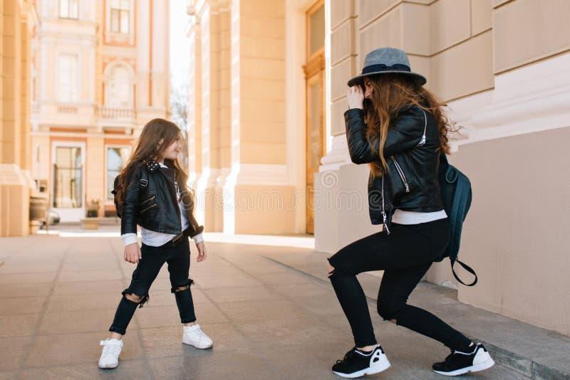 Nettes kleines Mädchen in den schwarzen Hosen mit Löchern auf den Knien, die auf der Straße, während ihre Mutter macht Foto aufwe stockfotos