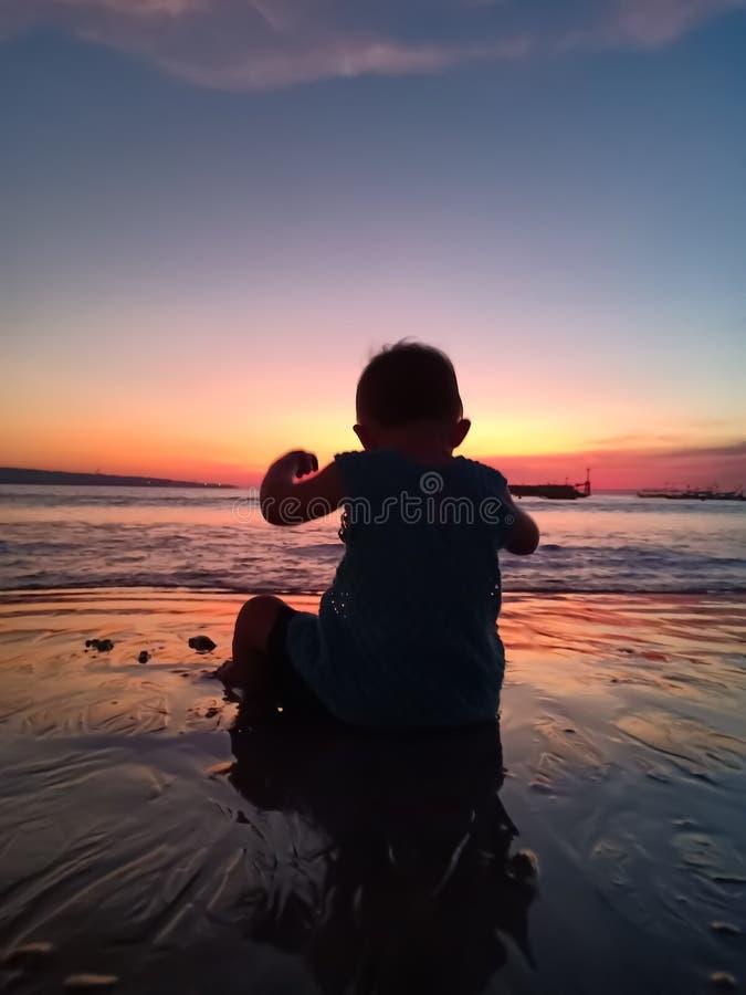 Nettes kleines Mädchen den Sonnenuntergang und den haben Spaß auf dem Strand treffen stockbilder