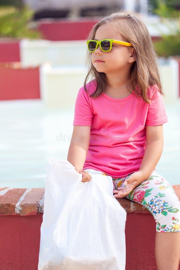 Nettes kleines Mädchen in der modernen Sonnenbrille nach dem Einkauf stockfoto