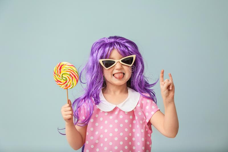 Nettes kleines Mädchen in der purpurroten Perücke und mit Lutscher auf Farbhintergrund lizenzfreies stockfoto