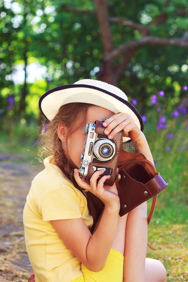 Nettes kleines Mädchen in der Retro- Ausstattung, die Fotos mit altem Film c macht stockbild