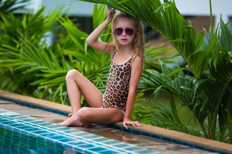 Nettes kleines Mädchen in der Sonnenbrille im Pool am sonnigen Tag stockfoto