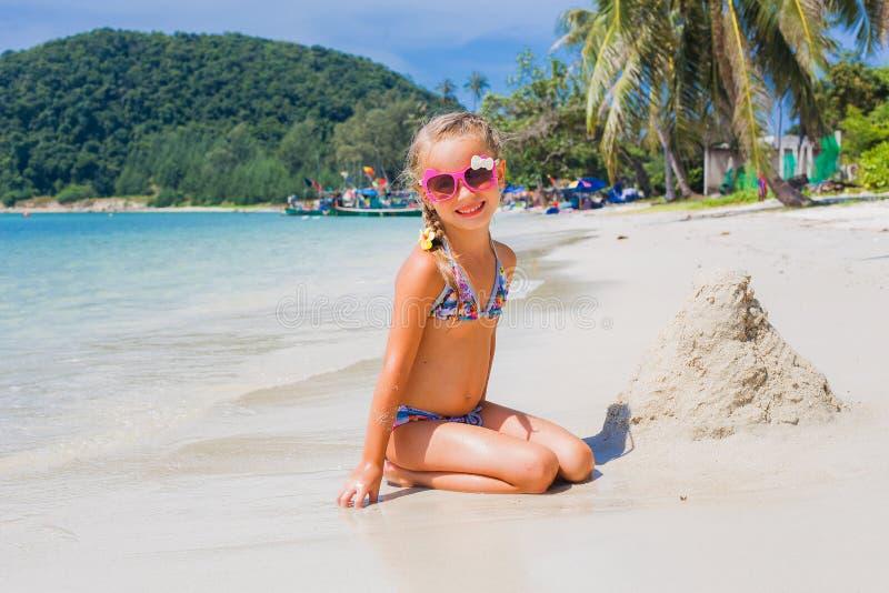 Nettes kleines Mädchen in der Sonnenbrille und in einem Badeanzug auf dem Strand im Paradies durch das Meer Reise und Ferien Getr stockbilder