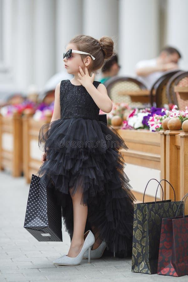 Nettes kleines Mädchen in der Sonnenbrille und in einem schönen Glättungskleid geht in einer prestigevollen Boutique stockbild