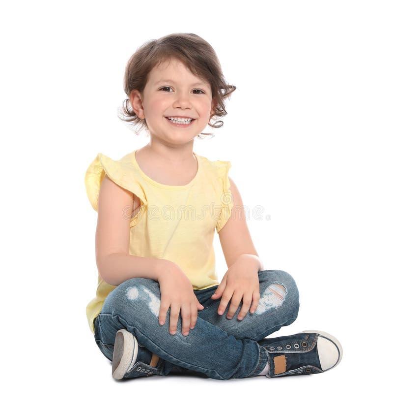 Nettes kleines Mädchen in der zufälligen Ausstattung, die auf Weiß sitzt stockfoto