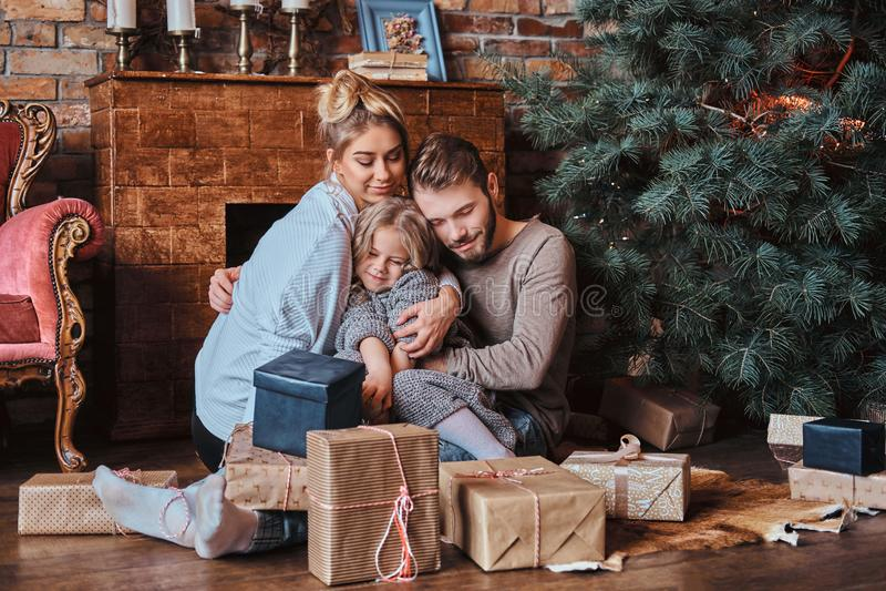 Nettes kleines Mädchen des Glückes, das mit ihren Eltern auf einem Boden umgeben durch Geschenke, nahe bei dem Kamin und dem Weih stockfotos