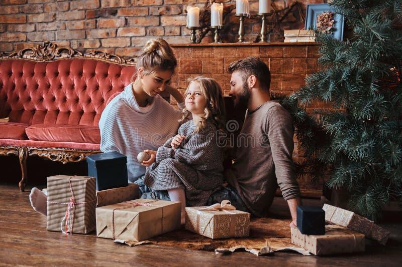 Nettes kleines Mädchen des Glückes, das mit ihren Eltern auf einem Boden umgeben durch Geschenke, nahe bei dem Kamin und dem Weih stockfotografie