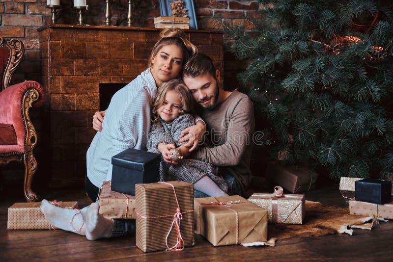 Nettes kleines Mädchen des Glückes, das mit ihren Eltern auf einem Boden umgeben durch Geschenke, nahe bei dem Kamin und dem Weih stockbilder