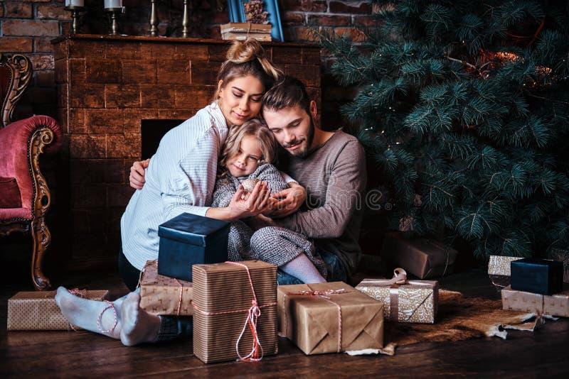Nettes kleines Mädchen des Glückes, das mit ihren Eltern auf einem Boden umgeben durch Geschenke, nahe bei dem Kamin und dem Weih lizenzfreie stockfotos