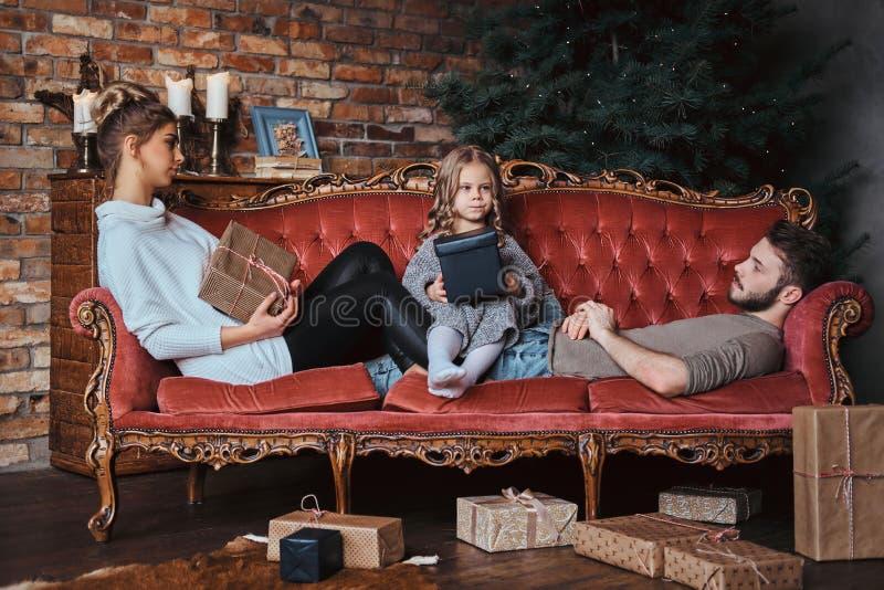 Nettes kleines Mädchen des Glückes, das mit ihren Eltern auf einem Weinlesesofa umgeben durch Geschenke sitzt stockbilder
