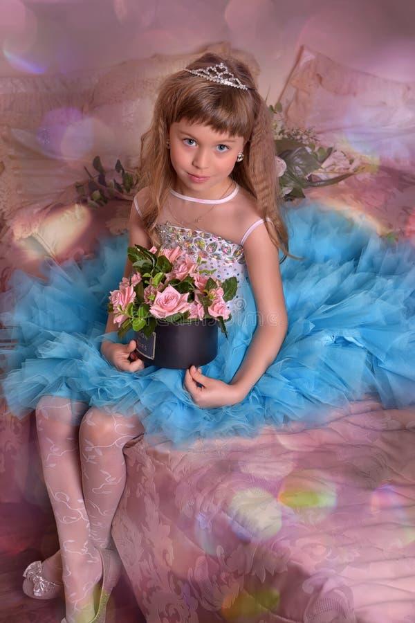Nettes kleines Mädchen in einem blauen Kleidersitzen lizenzfreies stockbild