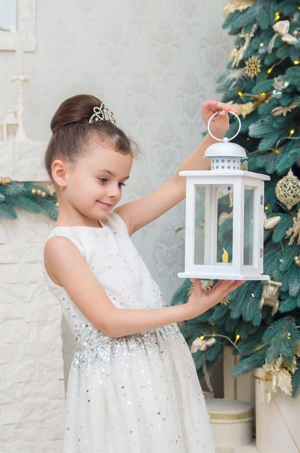 Nettes kleines Mädchen in einem weißen Kleid auf Weihnachtsabend ein d stockfoto