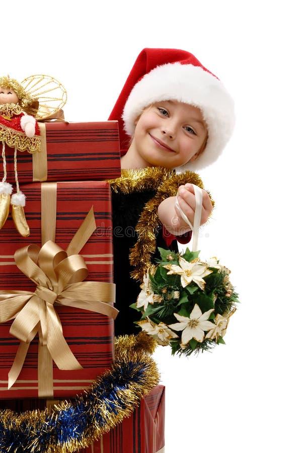 Nettes kleines Mädchen in einer Santa Claus-Kappe mit Weihnachtsgeschenken, Isolator lizenzfreie stockfotografie