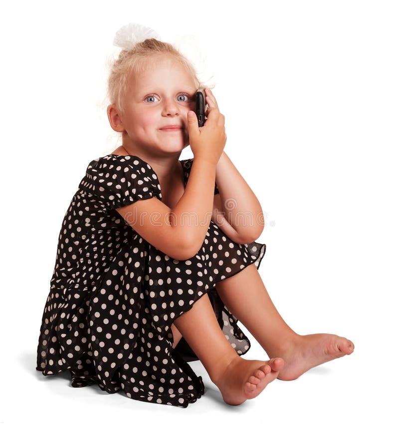 Nettes kleines Mädchen im dunklen Kleid mit den Tupfen lokalisiert stockbild