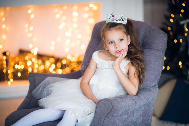 Nettes kleines Mädchen im intelligenten weißen Kleidweihnachten um den Kamin, der mit Feiertagsgirlande verzierte lizenzfreie stockbilder