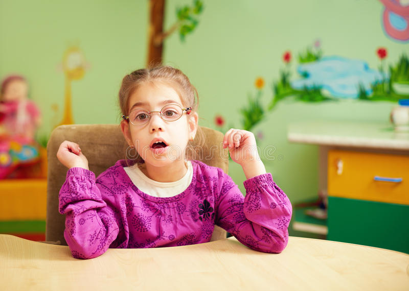 Nettes kleines Mädchen im Kindergarten für Kinder mit speziellem Bedarf stockfoto