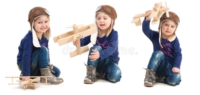 Nettes kleines Mädchen im Versuchshut mit hölzernem Flugzeug stockfotos