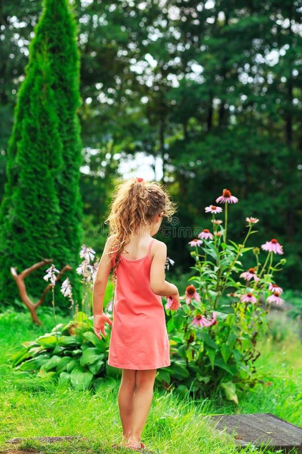 Nettes kleines Mädchen ist, träumend stehend und am Garten in warmem stockfoto