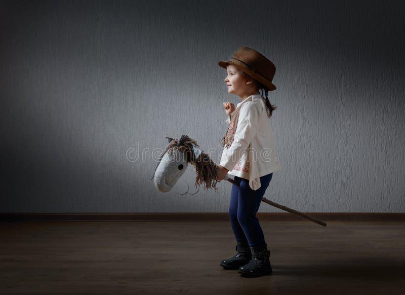 Nettes kleines Mädchen kleidete wie ein Cowboy an, der mit einem selbst gemachten h spielt stockbild