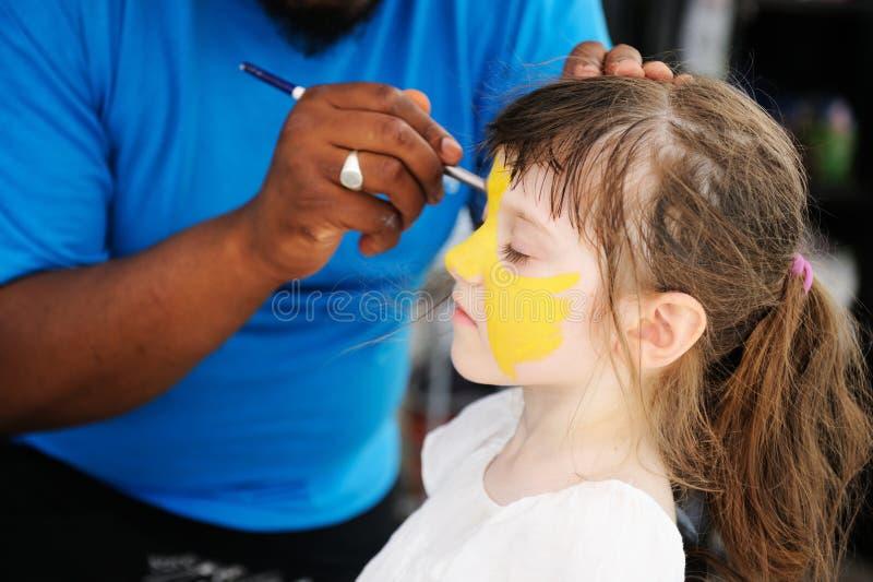 Nettes kleines Mädchen lässt ihr Gesicht malen lizenzfreies stockfoto