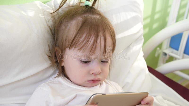 Nettes kleines Mädchen liegt auf Bett im Krankenhaus der Kinder und passt lustige Karikaturen auf dem Smartphone auf lizenzfreie stockfotos