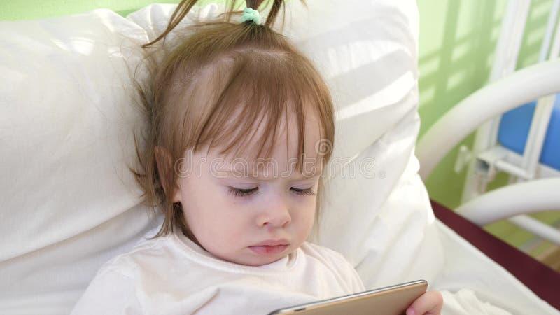 Nettes kleines Mädchen liegt auf Bett im Krankenhaus der Kinder und passt lustige Karikaturen auf dem Smartphone auf lizenzfreies stockbild