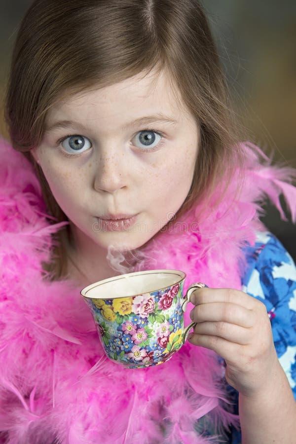 Nettes kleines Mädchen mit Blumenteeschale lizenzfreies stockbild
