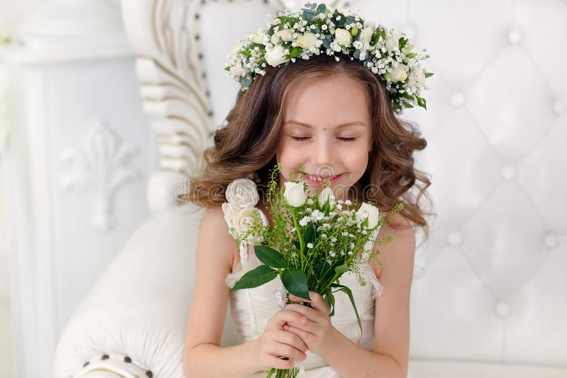 Nettes kleines Mädchen mit dem dunklen Haar in einem hellen Studio mit einer Krone von Blumen und in einem Blumenstrauß mit Augen stockbilder