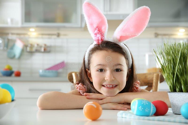 Nettes kleines Mädchen mit dem Häschenohrstirnband und gemalten Ostereiern, die bei Tisch in der Küche sitzen stockbild
