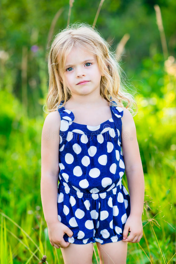 Nettes kleines Mädchen mit dem langen blonden gelockten Haar, Porträt im Freien lizenzfreies stockbild