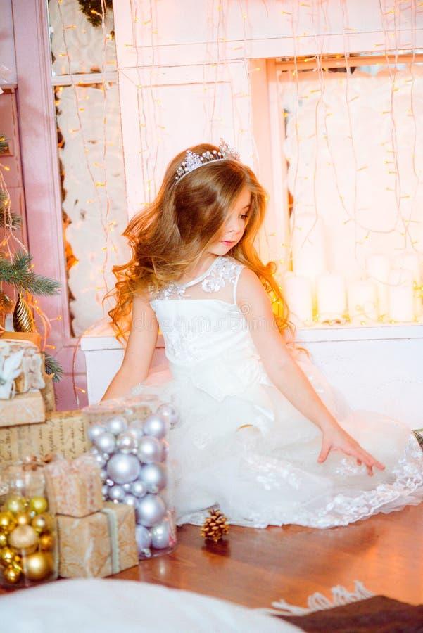 Nettes kleines Mädchen mit dem langen gelockten blonden Haar zu Hause nahe einem Weihnachtsbaum mit Geschenken und Girlanden stockfoto