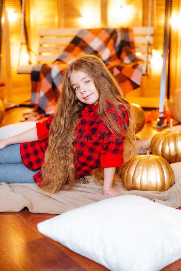 Nettes kleines Mädchen mit dem langen Haar in einem roten karierten Hemd in der Herbstlandschaft mit Kürbisen und gelben Blätt stockbilder