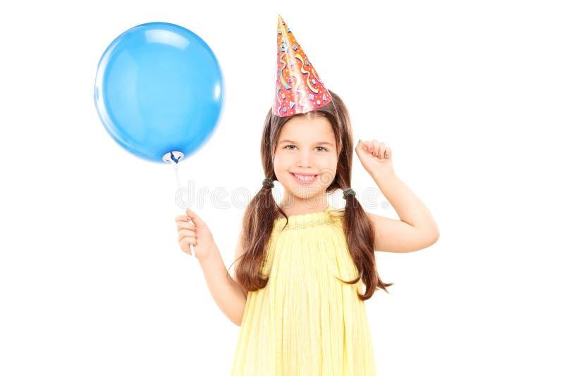 Nettes kleines Mädchen mit dem Parteihut, der Ballon hält lizenzfreies stockfoto