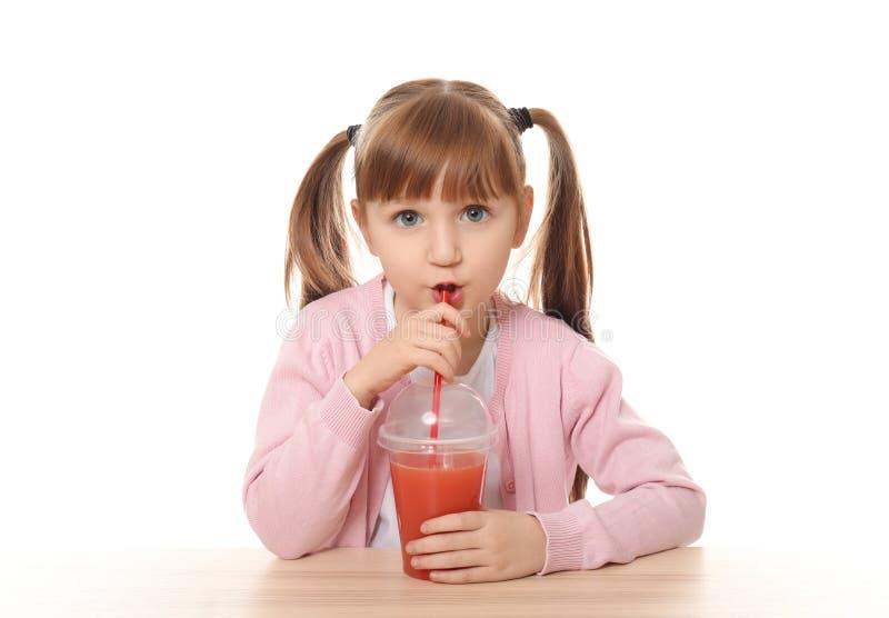 Nettes kleines Mädchen mit dem Zitrusfruchtsaft, der bei Tisch gegen weißen Hintergrund sitzt stockfotos