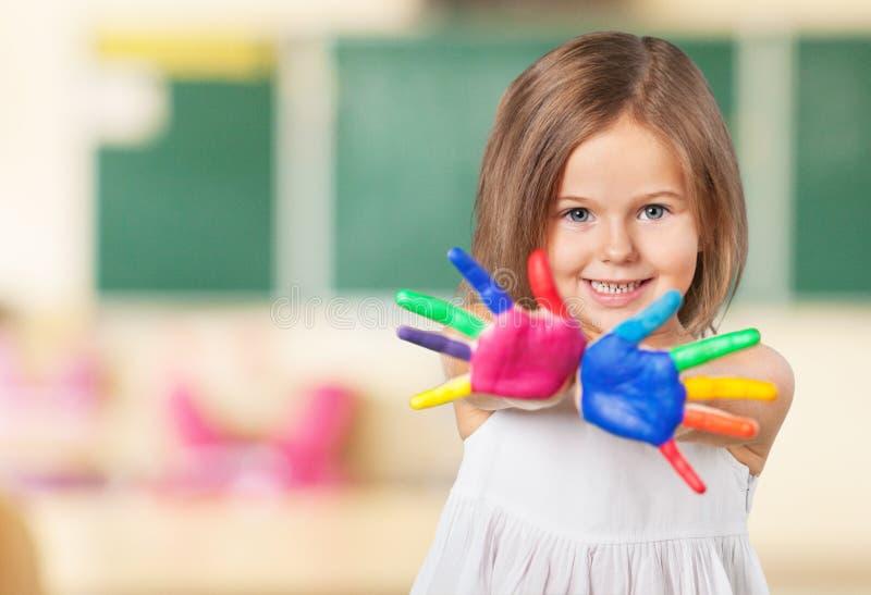 Nettes kleines Mädchen mit den bunten gemalten Händen an lizenzfreie stockfotografie