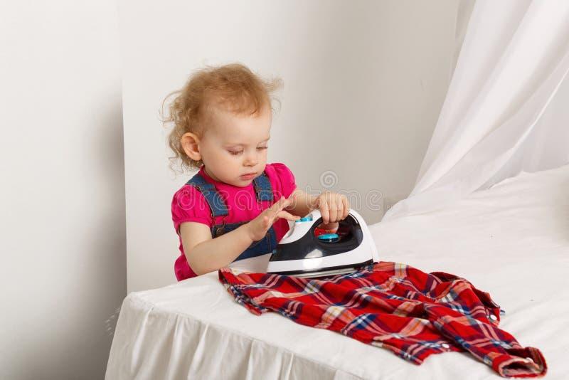 Nettes kleines Mädchen mit einem Eisen lizenzfreie stockbilder