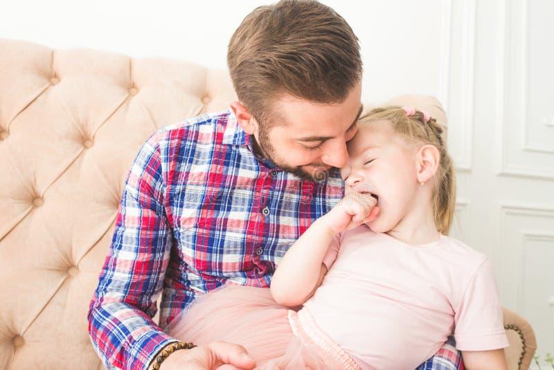 Nettes kleines Mädchen mit einem Lutscher, der mit Vati auf der Couch sitzt stockfoto