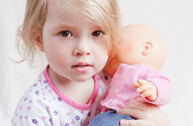 Nettes kleines Mädchen mit einer Puppe lizenzfreie stockfotografie