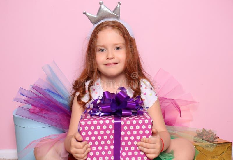 Nettes kleines Mädchen mit Geschenken für ihren Geburtstag auf Farbhintergrund stockbilder