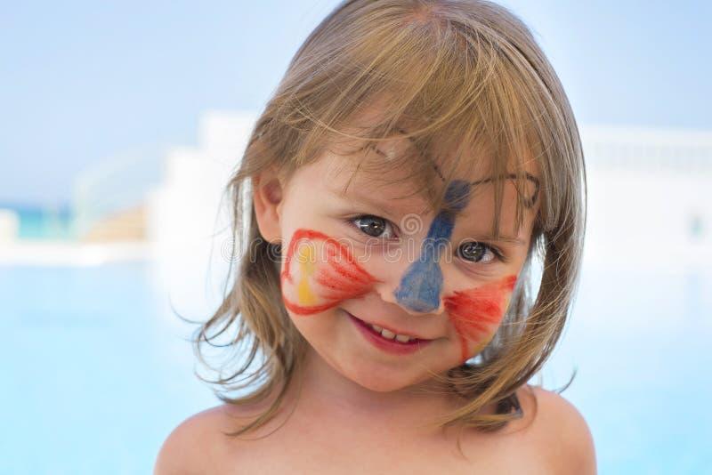 Nettes kleines Mädchen mit Gesicht malte tragenden Schmetterling stockfotografie